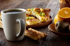 Morgenkonzept mit einem Tasse Kaffee, Breadsticks, Fruchttorten und Orangen auf hölzernem Hintergrund Lizenzfreies Stockfoto