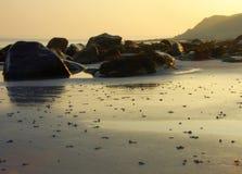 Morgenleuchte auf einem steinigen Strand Stockbild