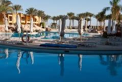 Morgenpoolseite im Hotel Keine Leute nähern sich Swimmingpool Geschlossene Poolregenschirme Wasserpoolreflex im ruhigen Wasser Pa Lizenzfreies Stockbild