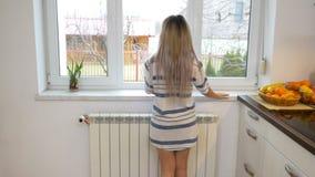 Morgenprogramm mit der hübschen Frau, die Kessel auf elektrischen Gewindebohrer setzt und auf dem Fenster schaut stock footage