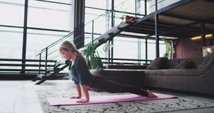 Morgens übendes Yoga sportlicher attraktiver Dame zu Hause, das urdhva mukha shvanasana Übung, aufwärts gegenüberstellend ausdehn stock footage
