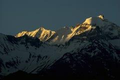 Morgensonnen-Lichtglanz an der Spitze des Schneespitzen-Gebirgsgipfels Stockfotos