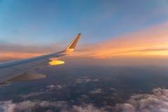 Morgensonnenaufgang mit Flügel eines Flugzeugfliegens über Wolken Reisendes Konzept Stockfotos