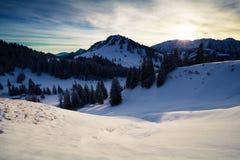 Morgensonnenlicht über schneebedeckten Bergen stockbild
