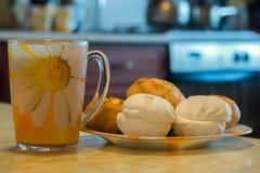 Morgentee in einem gelben Becher mit Eibischen und Brötchen stockfotografie