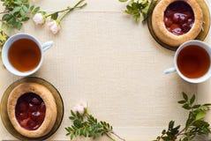 Morgentee mit Backwaren, rosafarbene Blumen auf dem Tisch Kuchen mit Erdbeeren Auf einer alten Serviette Stockbilder