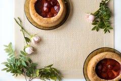 Morgentee mit Backwaren, rosafarbene Blumen auf dem Tisch Kuchen mit Erdbeeren Auf einer alten Serviette Stockfotografie