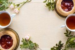 Morgentee mit Backwaren, rosafarbene Blumen auf dem Tisch Kuchen mit Erdbeeren Auf einer alten Serviette Lizenzfreie Stockbilder