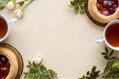 Morgentee mit Backwaren, rosafarbene Blumen auf dem Tisch Kuchen mit Erdbeeren Auf einer alten Serviette Lizenzfreies Stockfoto