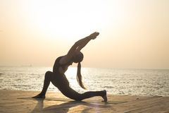 Morgentraining von Yoga auf dem Sommerstrand stockbild