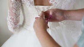 Morgenvorbereitungen Frau, die auf Kleid sich setzt stock footage
