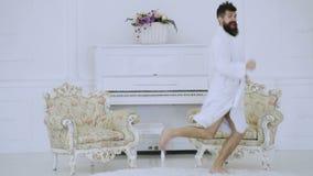 Morgonövningsbegrepp Den uppsökte mannen i en vit klä kappa kör i ett rum mot en vit pianobakgrund Begrepp arkivfilmer