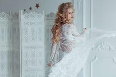 Morgon av bruden Den härliga unga kvinnan i den vita negligé som spelar med, skyler klänningen framkallar i vinden lycklig flicka Royaltyfri Bild