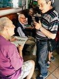 Morgon en vänlig konversation av äldre män på kafét Arkivbild