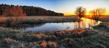 Morgon gryning nära en pittoresk flod arkivfoto