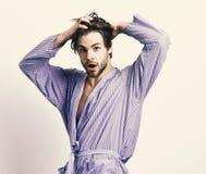 Morgon och duschabegrepp Man med skägget i blå dressingkappa på grå bakgrund Skäggigt macho i blå badrock Royaltyfria Bilder