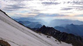 Morgon- och gryningatmosfär i fjällängarna av Schweiz med en brant glaciär i förgrunden och raderna av disig bergbehin arkivfoto