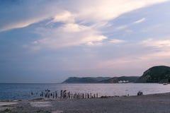 Morgon på havet med härliga vitmoln, den bergiga kustlinjen och den steniga kusten Royaltyfria Foton