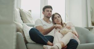 Morgon tillsammans för ett par som hållande ögonen på tv och ätapopcorn på pyjamas som sitter på hemtrevlig soffastil lager videofilmer