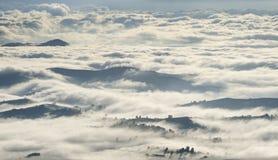 Morgonen fördunklar över berg, skogar och byar Royaltyfria Bilder