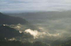 Morgonen fördunklar över byar och skogar Arkivfoto