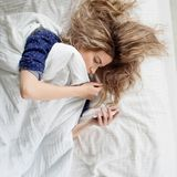 Morgonen kvinnan under filten, vänder av ringklockan eller att hålla ögonen på det sociala nätverket Arkivfoto