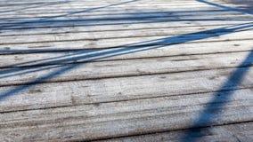 Morgonfrost på träbryggan som göras av bräden Vinterträbakgrund arkivfoton