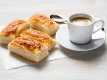 Morgonfrukost med nya rullar av smördeg och koppen kaffe på den vita trätabellen Arkivbilder