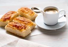 Morgonfrukost med nya rullar av smördeg och koppen kaffe på den vita trätabellen Arkivfoto