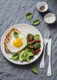Morgonfrukosttabell Det stekte ägget grillade smörgåsen och spenat, tomaten, avokadosallad på en grå bakgrund arkivbilder