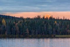 Morgonhöstlandskap med moonset och sjön Arkivfoto