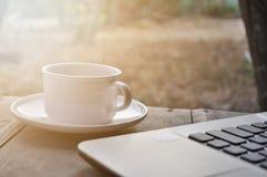 Morgonkaffe med bärbara datorn royaltyfria foton