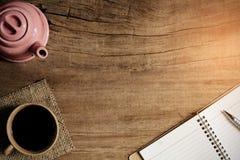 Morgonkaffe- och bokpenna på den gamla wood tabellen Arkivfoton