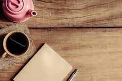 Morgonkaffe- och bokpenna på den gamla wood tabellen Royaltyfri Foto