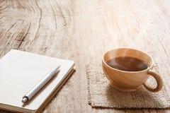 Morgonkaffe- och bokpenna på den gamla wood tabellen Arkivbild