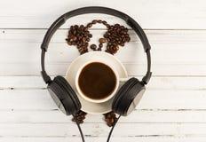 Morgonkaffe och musikbegrepp med hörlurar royaltyfria foton