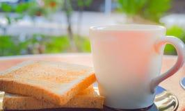 Morgonkaffe och rostat bröd för helt vete på den svarta plattan på den röda tabellen med rök över koppen kaffe i solskenet Royaltyfria Bilder