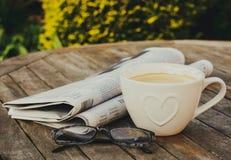 Morgonkaffe och tidningar arkivbild
