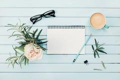Morgonkaffekopp, ren anteckningsbok, blyertspenna, glasögon och tappningrosblomma i vas på över huvudet sikt för blått lantligt s Arkivfoton