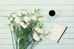 Morgonkaffekopp, tom pappers- lista, blyertspenna och bukett av eustomaen för vita blommor på blå lantlig bästa sikt för tabell L fotografering för bildbyråer