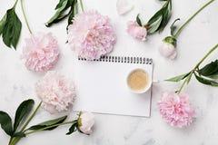 Morgonkaffekoppen för frukost, den tomma anteckningsboken och rosa färgpionblommor på den vita bästa sikten för stentabellen i lä Royaltyfri Fotografi