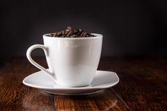 Morgonkaffekoppen fyllde med kaffebönor på tabellen Arkivbilder