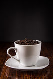 Morgonkaffekoppen fyllde med kaffebönor på tabellen Arkivbild