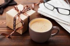 Morgonkopp kaffe, gåva, tidning, exponeringsglas och bowtie på träskrivbordet för frukost på lycklig faderdag Arkivbilder