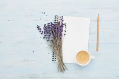 Morgonkoppen kaffe, den rena anteckningsboken och lavendel blommar på bästa sikt för blå bakgrund Funktionsdugligt skrivbord för  royaltyfri fotografi
