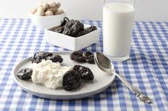 Morgonlynnet, den sunda frukosten innehåller keso, jordnötter, katrinplommoner, exponeringsglas av mjölkar produkten som lägger t arkivfoton