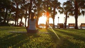 Morgonmeditationen i parkera, kvinna öva yoga på kusten, skott på dropp för fläck för Canon EOS 5D i ultrarapid Full HD 1080 arkivfilmer