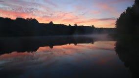 Morgonmist över floden och vaggar, sommargryning, himlen reflekterad i vattnet stock video