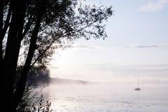 Morgonmist över sjön med segelbåten Royaltyfri Bild