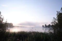 Morgonmist över sjön med segelbåten Royaltyfria Bilder